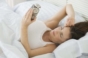 Hispanic woman looking at alarm clock